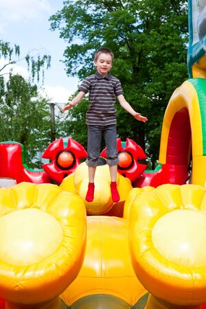 Young boy jumping on inflatable playground photo
