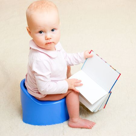 poo: Little baby girl sitting on blue potty with open book Stock Photo
