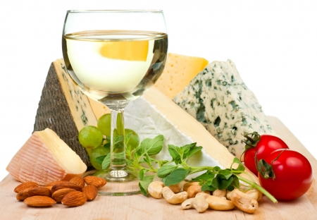 cheese platter: Glass of white wine with various types of cheese and garnishes