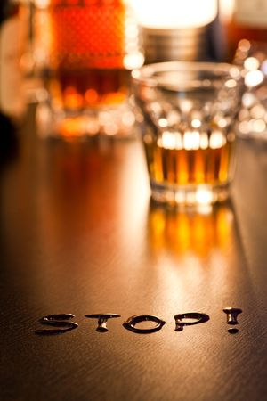 The word Stop with glass of  whiskey in background, shallow DOF photo