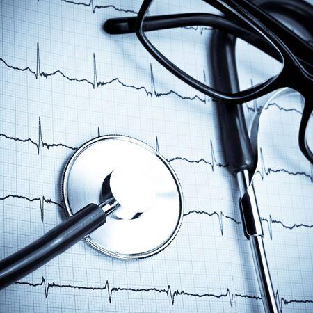blue toned: Stethoscope and glasses lying on ECG diagram blue toned Stock Photo