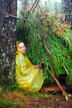 turismo ecologico: Joven llevaba impermeable amarillo sentado en un refugio de ramas Foto de archivo