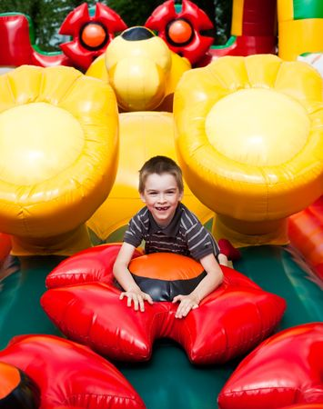 Young boy playing in inflatable playground photo
