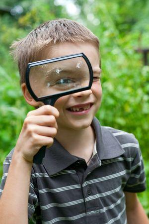 thru: Young boy looking thru hand magnifier, shallow DOF