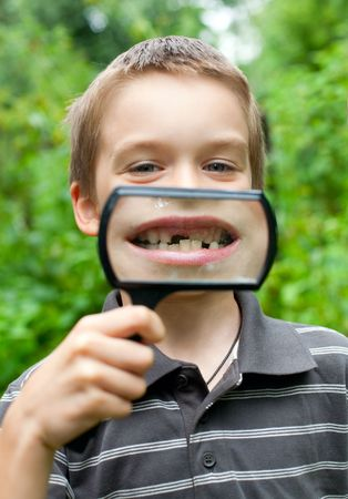 Young boy showing missing tooth through hand magnifier, shallow DOF photo
