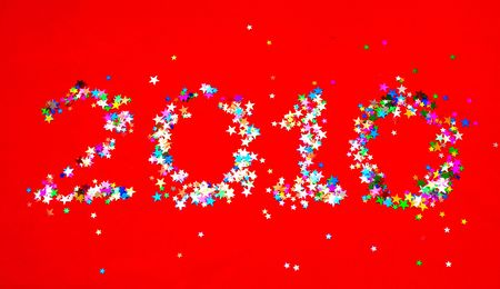 Star confetti in the shape of number 2010 on red background photo