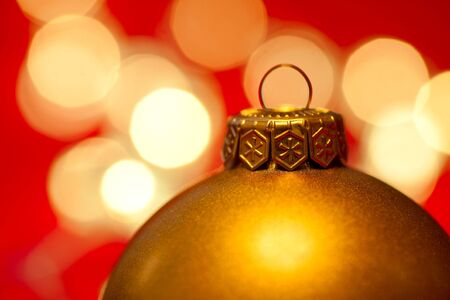 Golden Christmas bauble with blured lights in background, very shallow DOF photo
