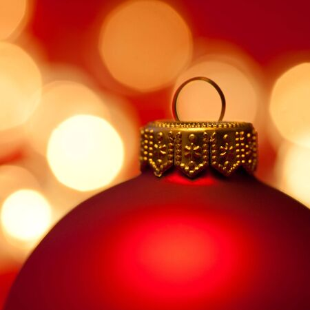 Red Christmas bauble with blured lights in background, very shallow DOF photo