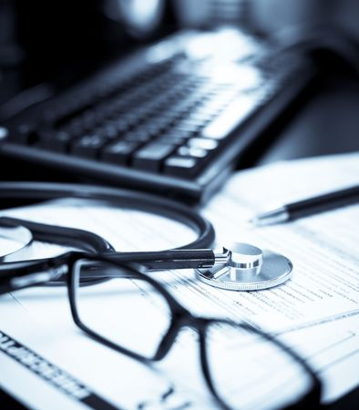 Stethoscope on a prescription form with glasses pen and keyboard, very shallow DOF photo
