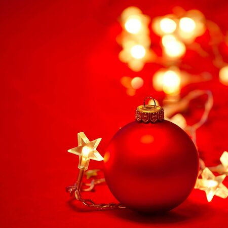 Red Christmas bauble with star-shaped lights  on red background, shallow DOF photo