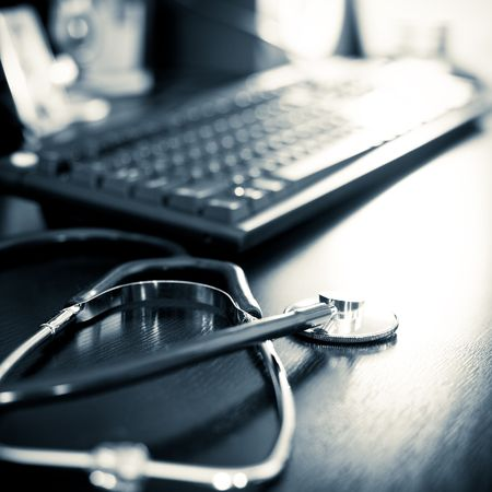 doctors tools: Stethoscope on a table with keyboard, very shallow DOF