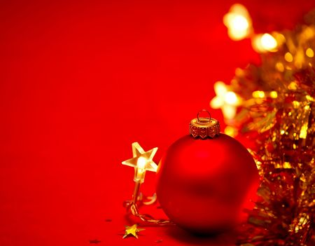 Red Christmas bauble with star-shaped lights and tinsel on red background, shallow DOF photo