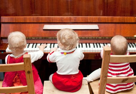 duet: Three little baby girls playing a piano Stock Photo