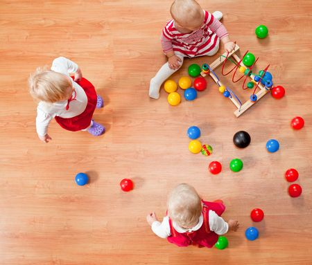 Top view of three little girls playing on the floor photo
