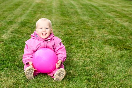 Cute little baby girl wearing pink suit sitting with pink ball on lawn photo