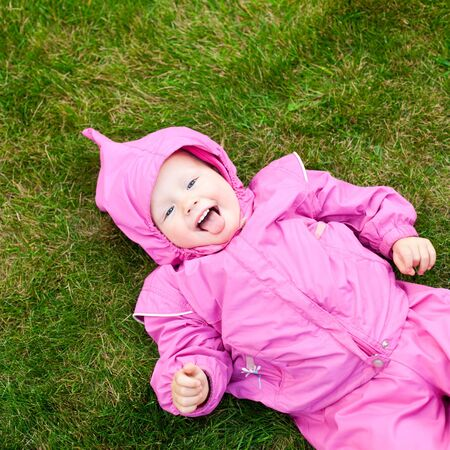 Cute little baby girl wearing pink suit lying on lawn outdoors photo