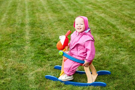 rocking horse: Cute little baby girl wearing pink suit sitting on rocking horse outdoors