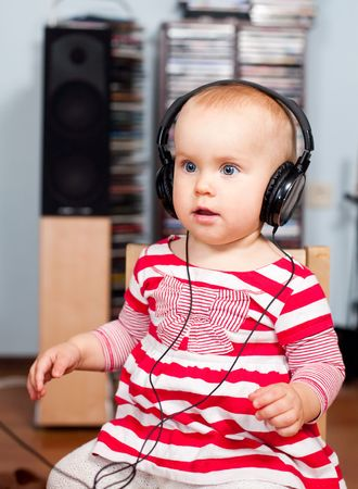 Cute little baby girl listening to a music photo