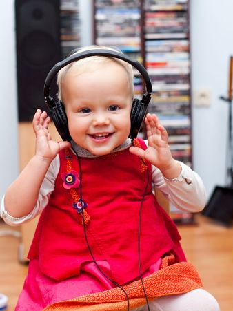Cute baby girl listening to a music photo