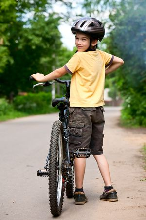 Young boy standing with bicycle, shallow dof Stock Photo