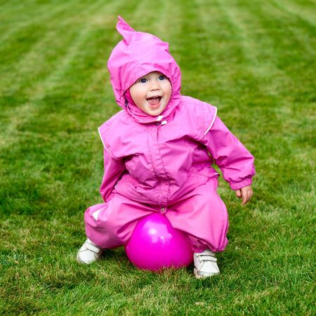 Cute little baby girl wearing pink suit playing with pink ball on a lawn photo