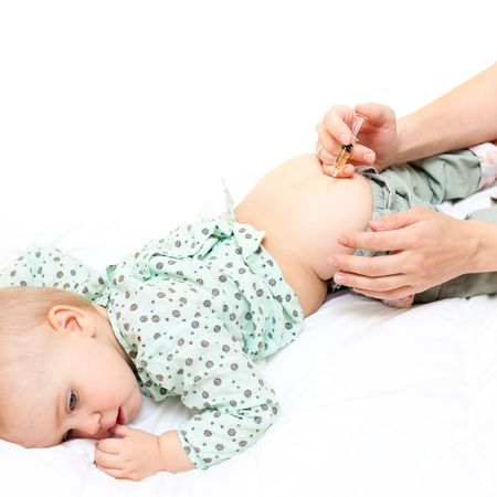intramuscular: Doctor giving a child an intramuscular injection, shallow DOF Stock Photo
