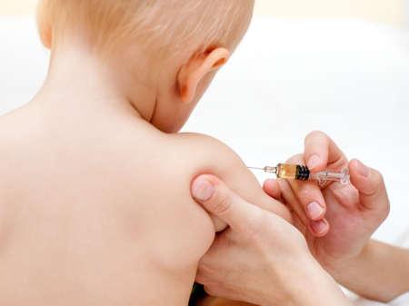 inyeccion intramuscular: M�dico que den a un ni�o una inyecci�n intramuscular en el brazo, someras DOF