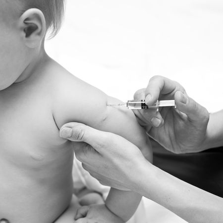 contagion: Doctor giving a child an intramuscular injection in arm, shallow DOF