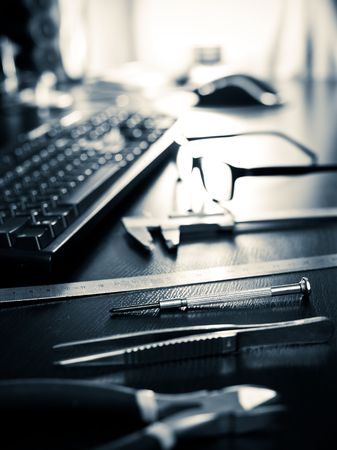 Screwdriver, pincers, ruler, caliper with keyboard and glasses on a table, very shallow DOF photo