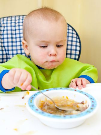 Little baby girl eating with spoon in a highchair Stock Photo - 5826399