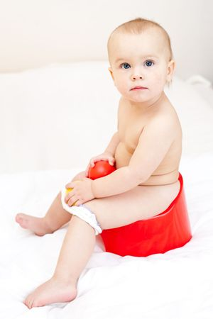 Cute little baby girl sitting on red potty photo
