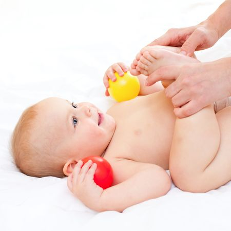 Mother massaging her little baby girl, shallow focus photo