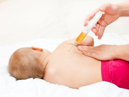 inyeccion intramuscular: Doctor dar a un ni�o una inyecci�n en el om�plato, someras DOF Foto de archivo