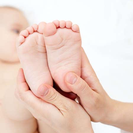 Masseur massaging little babys feet, shallow focus photo