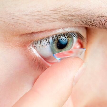 eye lens: Young woman Inserting a contact lens closeup