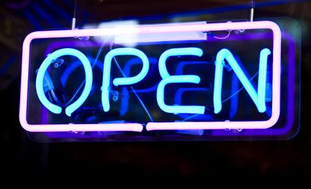 Glowing open neon sign in a window Stock Photo