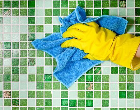 huis opruimen: Hand in gele beschermende hand schoen mozaïek muur reinigen