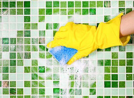 limpieza del hogar: Mano en amarillo guante protector, limpieza de pared de mosaico