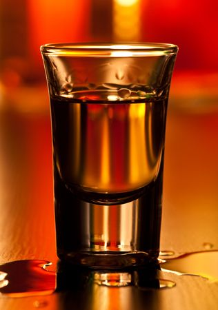 hard liquor: Shot glass of whiskey on a table, shallow focus Stock Photo