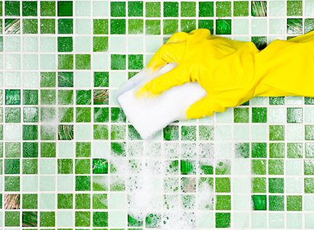Hand in yellow protective glove  cleaning mosaic wall photo