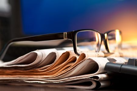 news paper: Glasses on stack of newspapers, very shallow focus