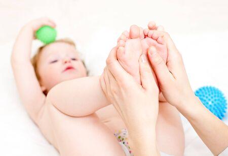 Masseur massaging childs feet, shallow focus photo