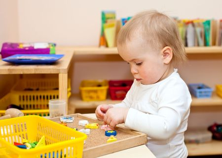 Little baby girl playing with wooden toys at nursery