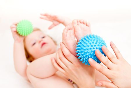 Masseur massaging childs feet with rubber device, shallow focus photo