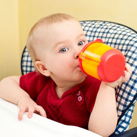 highchair: Little baby girl sitting in a highchair with plastic drinking cup Stock Photo
