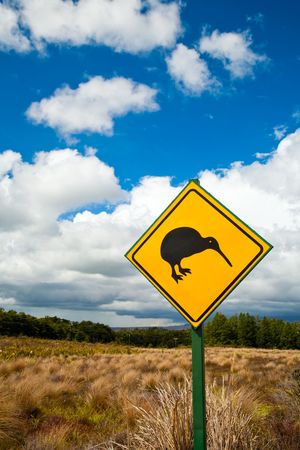 flightless bird: Kiwi crossing road sign against cloudy sky at New Zealand