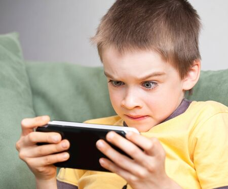computer game: Young boy playing handheld game console