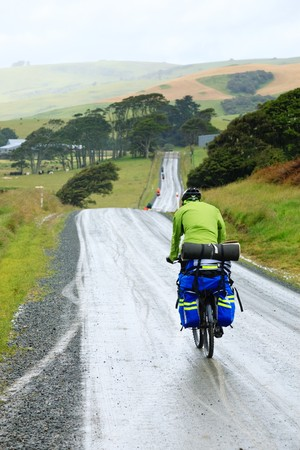 Cycle tourists on a dirt road in New Zealand photo