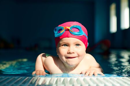 Happy little girl looking out from swimming pool photo