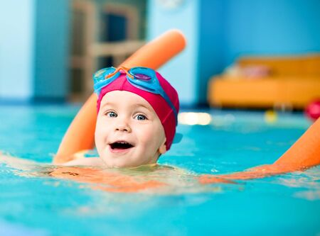 girl swimming: Happy little girl learning to swim with pool noodle